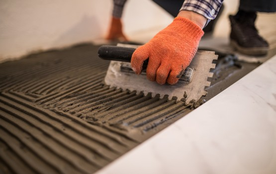 Troweling mortar onto a concrete floor in preparation for laying white floor tile.